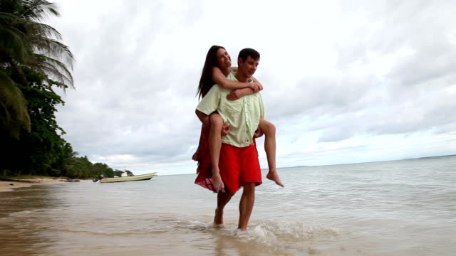 Man carrying woman on sand tropical beach.