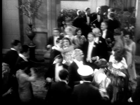 1928 b/w ha ws man carrying woman quickly through crowded black tie event to elevator  - actor stock videos & royalty-free footage