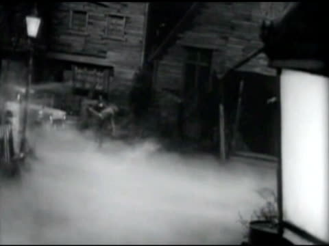 ws man carrying   woman's body through fog / united states - 1960 stock-videos und b-roll-filmmaterial