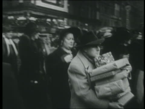 vidéos et rushes de b/w 1950 pan man carrying xmas presents on busy sidewalk trips - carrying
