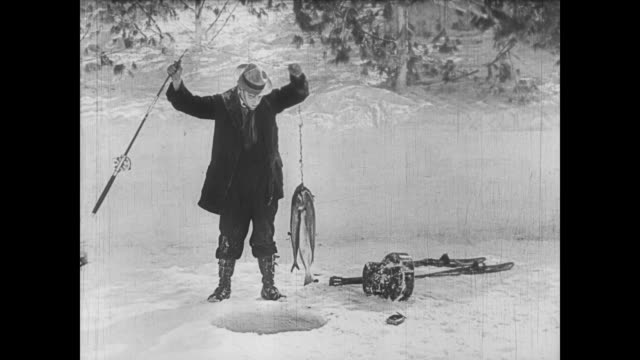 1922 man (buster keaton) carves out ice hole to fall in before accidentally catching someone else's fish - fangen stock-videos und b-roll-filmmaterial