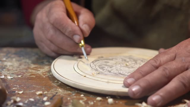 Man carving decorative wall plate