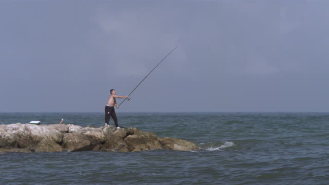 slo mo man casting fishing line from breakwater, spain, wa - cast member stock videos & royalty-free footage