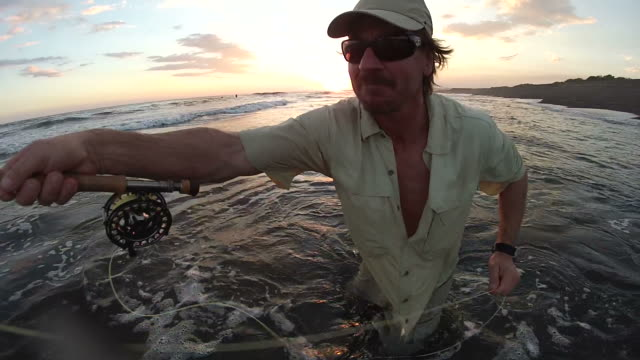 MS Man casting fly rod in surf at sunset / Iztapa, Guatemala