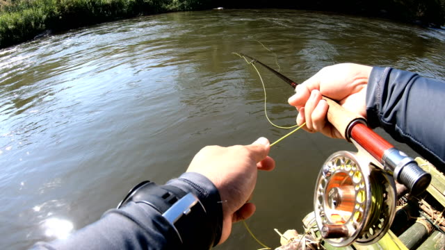 man casting-fly fishing on a bamboo raft. - fishing reel stock videos and b-roll footage