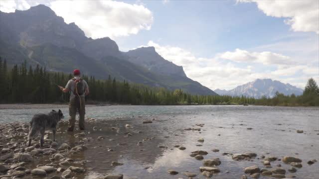 vídeos de stock, filmes e b-roll de homem lança linha de pescar no córrego da montanha - só um homem maduro