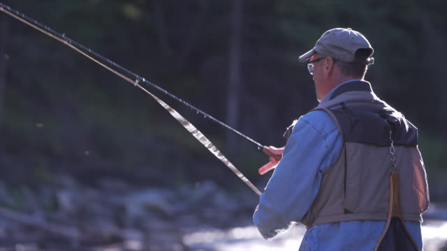 Man casts fly fishing line into mountain stream