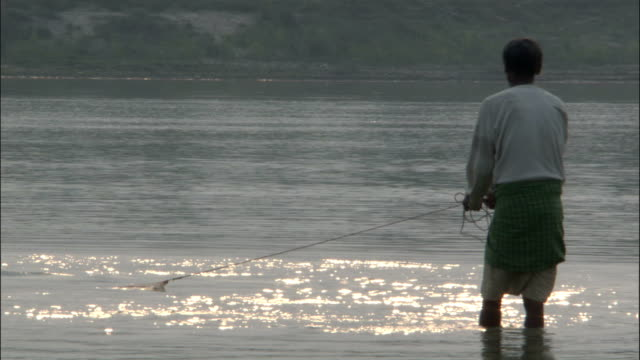 man casts net into ganges available in hd. - fishing net stock videos & royalty-free footage
