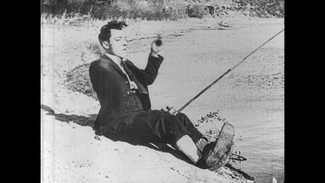1921 man (buster keaton) catches a large fish and attempts to use it as bait, but it's too strong and pulls keaton into the water while breaking the fishing pole - 1921 stock-videos und b-roll-filmmaterial