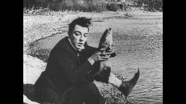 1921 man (buster keaton) catches a small fish and uses it as bait to catch a larger one - 1921 stock-videos und b-roll-filmmaterial