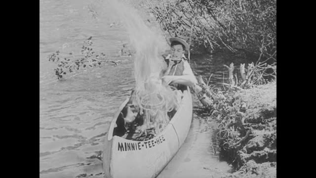 vídeos de stock, filmes e b-roll de 1923 man (buster keaton) catches fish and tries to cook it in a canoe - fardo
