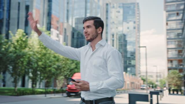 uomo che cattura un uber nel centro della città. uso dell'app per dispositivi mobili - taxi video stock e b–roll