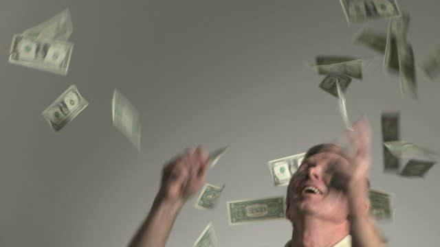 man catching money falling from the sky