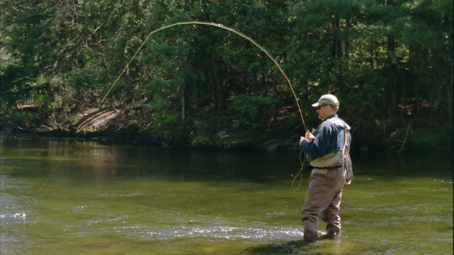 WS Man catching Salmon fly fishing on Grand Lake Stream / Maine, USA