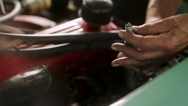 a man changes a spark plug in a classic car - work tool stock videos & royalty-free footage