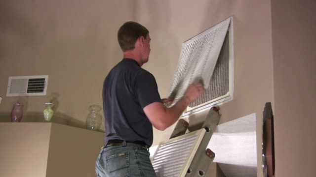 Man changes air filter in house
