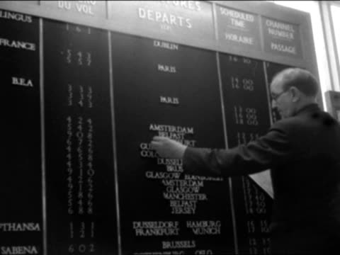 man changes the details on a departure board at london aiport. - hinweisschild stock-videos und b-roll-filmmaterial