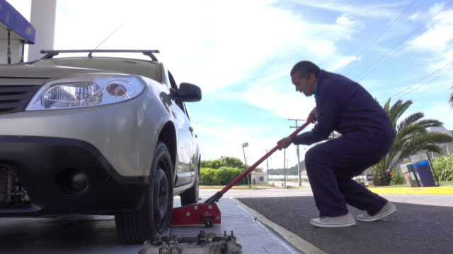 Man changing a flat tire using a hydraulic floor jack