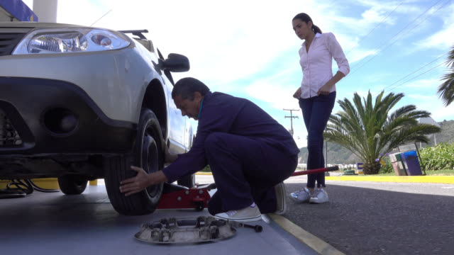 man changing a flat tire using a hydraulic floor jack - lug wrench stock videos and b-roll footage