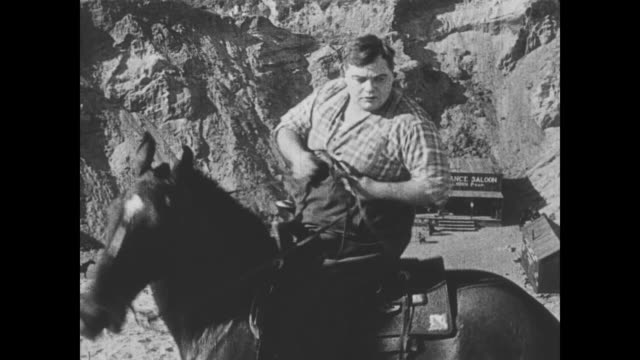 1918 man (fatty arbuckle) chases after wild bill hiccup on a horse, and another man (buster keaton) has gunfight in the canyon - hiccup stock videos and b-roll footage