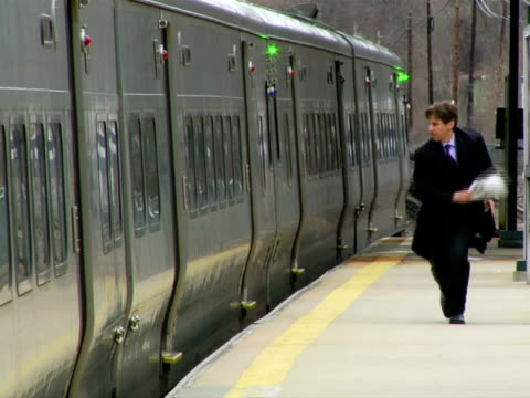 ms, man chasing for train on station platform, chappaqua, new york state, usa - fallimento video stock e b–roll