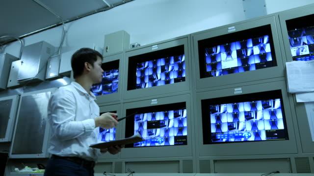 セキュリティ監視システムのモニターでチェックする男 - real time点の映像素材/bロール