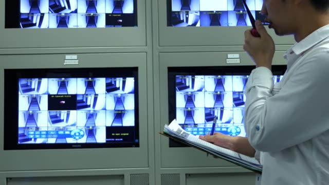 セキュリティ監視システムのモニターでチェックする男 - 24コマ撮影点の映像素材/bロール