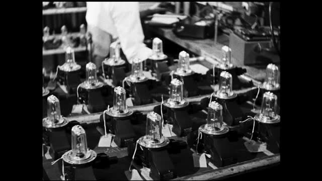 vidéos et rushes de man checking bulb assemblies and zoom in view of table full of bulb assemblies - 1940 1949
