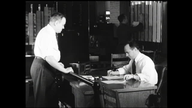vídeos y material grabado en eventos de stock de man checking file cards on the wall, time stamping them, and put them inside bin on conveyor belt; man checking paperwork behind desk as another... - 1940 1949