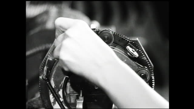 vidéos et rushes de man checking for precision on machine; different views of lots of women working inside factory, operating lathe machines; hands placing metal under... - 1940 1949