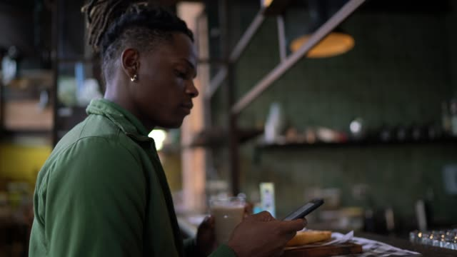 man checking his smartphone while taking breakfast in a cafeteria - dreadlocks stock videos & royalty-free footage