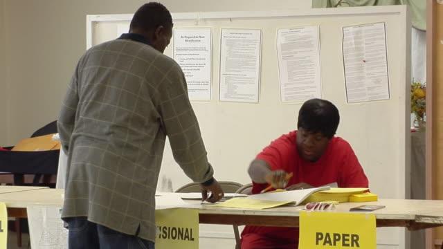 vídeos de stock, filmes e b-roll de ms, zo, man checking in at desk at polling place, toledo, ohio, usa - título de eleitor