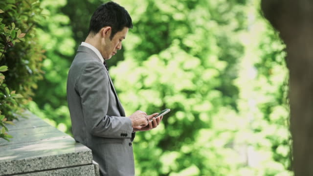 Man Checking Phone in Park