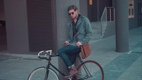 man checking phone in urban setting - waiting stock videos & royalty-free footage