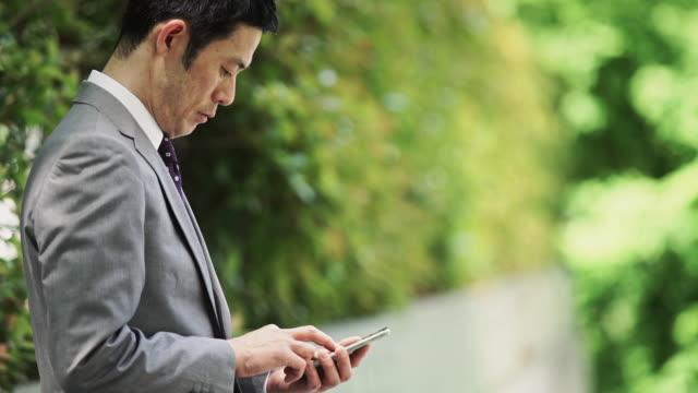 man checking phone on tree lined street - portability点の映像素材/bロール