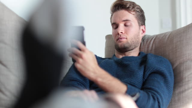 Man checking smartphone at home on sofa