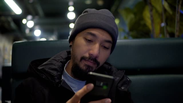 man checking smartphone in cafe at night - piercing video stock e b–roll