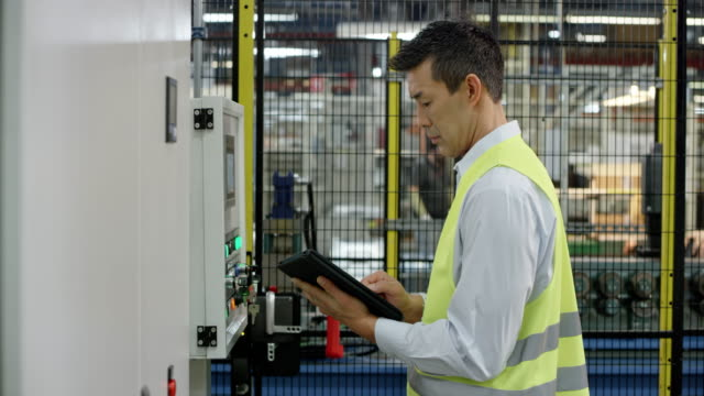 man checking the data on the machine's lcd screen in the factory and comparing it to the data on the tablet - attrezzatura industriale video stock e b–roll