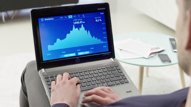 vidéos et rushes de ds homme vérifiant les statistiques d'une valeur de cryptocurrency sur son ordinateur portable - prendre sur les genoux