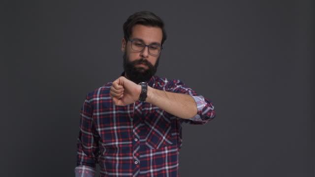 man checking the time at studio shot/ debica/ poland - assuefazione video stock e b–roll