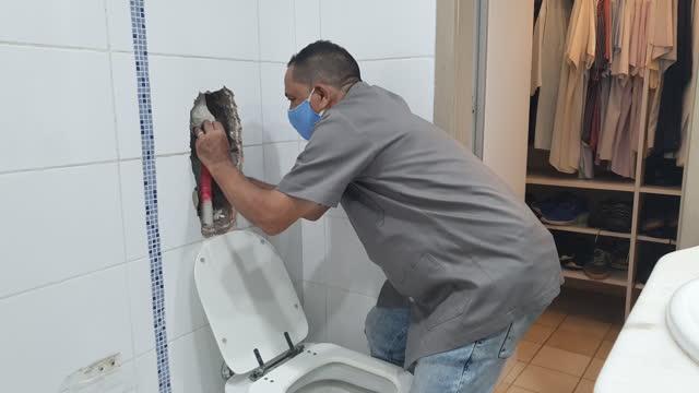 vídeos de stock, filmes e b-roll de homem verificando o lavador de banheiro usando máscara - máscara