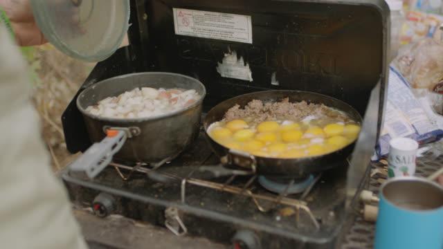 vídeos y material grabado en eventos de stock de cu. man checks potatoes boiling in cooking pot on portable gas grill with sausage and eggs sizzling in skillet. - receta instrucciones