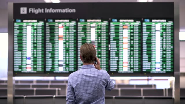 vídeos de stock e filmes b-roll de man checks the departure board at the airport while talking on the phone - time-lapse - anticipation