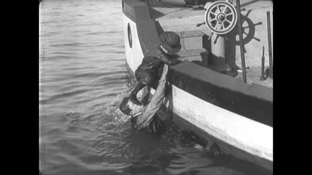 1921 Man (Buster Keaton) checks water temperature before jumping in to save drowning boy