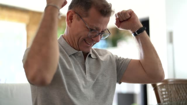 Man cheering good results at home office