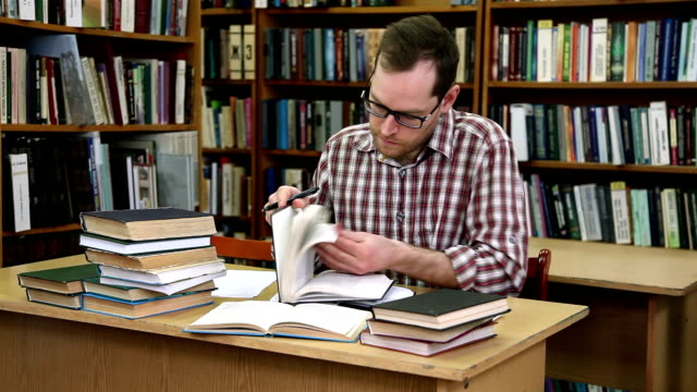 stockvideo's en b-roll-footage met man cheking boeken in de bibliotheek - literature