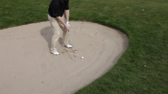 man chipping out of sand bunker, uk - golf stock-videos und b-roll-filmmaterial