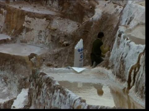 Man chips away at wall for salt Inca Salt Pans Peru