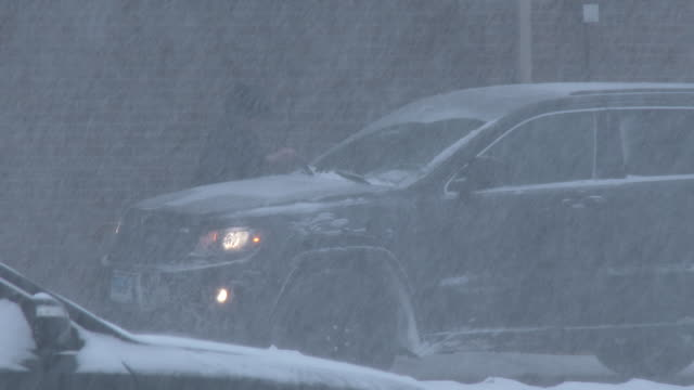 A man chips snow and ice off of his windshield wipers in Waterbury Connecticut as very heavy snow continues to fall during an intense blizzard