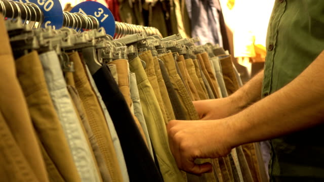 Man Choose A Clothing In Retail Store